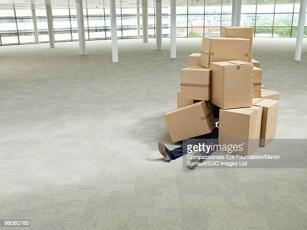 mans legs sticking out from a pile of boxes