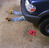 Man's legs sticking out from under body of car, elevated view