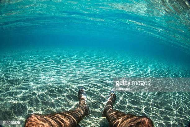 Man's legs underwater in the ocean