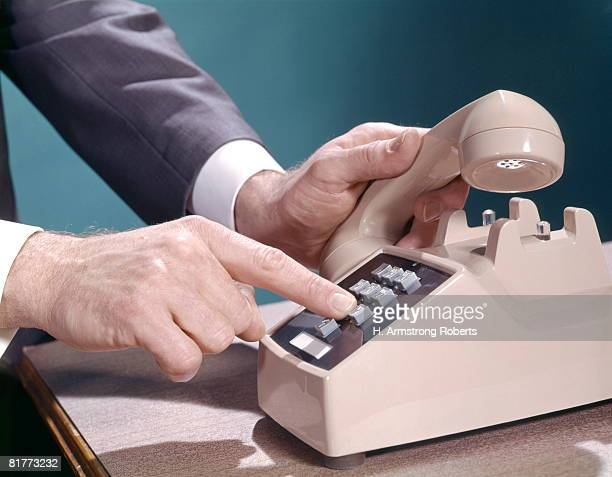 Mans Male Hands Lifting Receiver Push Buttons On Beige Telephone Dial Dialing Telecommunications Retro Vintage.