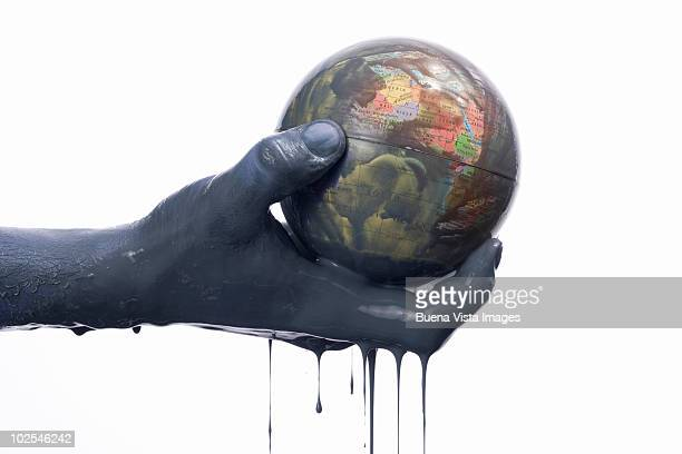 Man's oily hands with oily globe