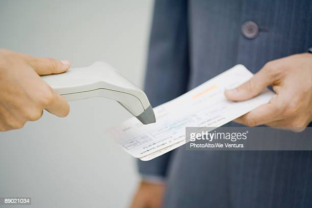 Man's plane tickets being scanned