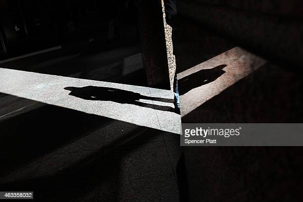 A man's shadow is viewed as he has a cigarette outside of a midtown building on a bitterly cold day on February 13 2015 in New York City In New York...