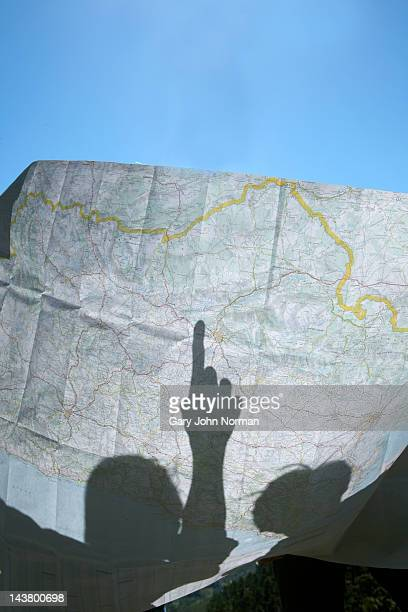 mans shadow pointing at map