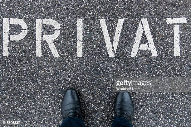 Mans shoes standing on private parking area