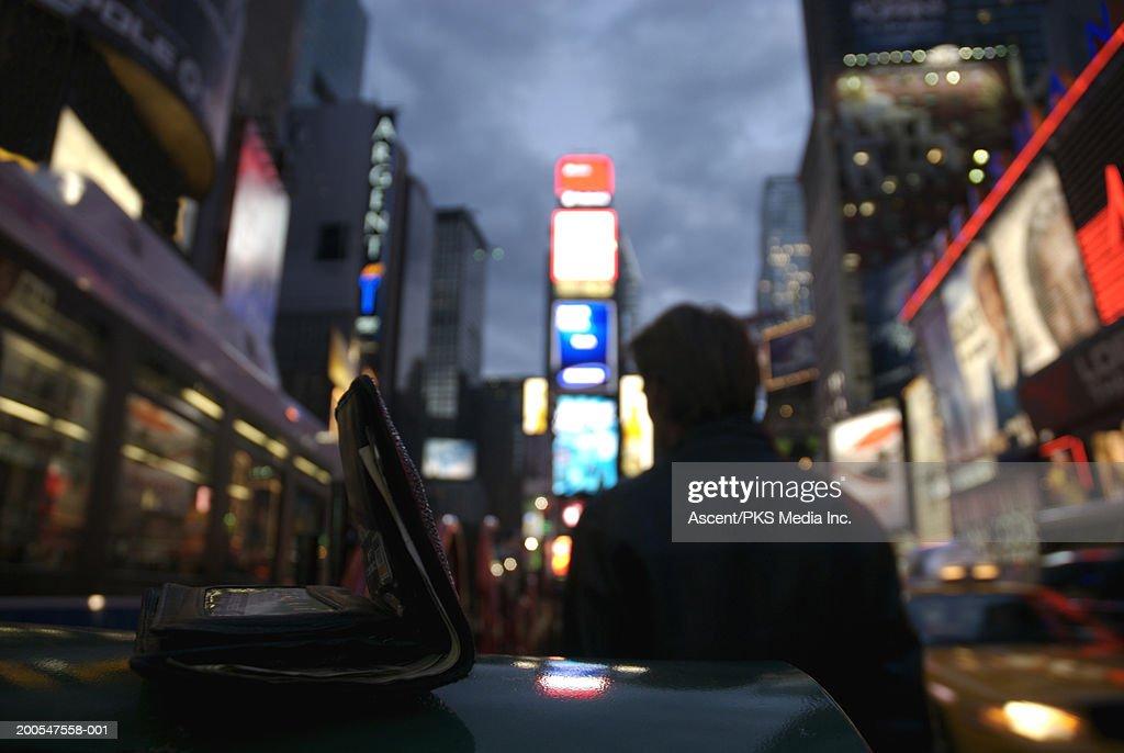 Man's wallet lying on ledge, with man walking away : Stock Photo