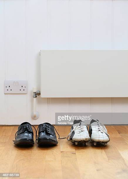 Mans work and football boots in a row in the hall