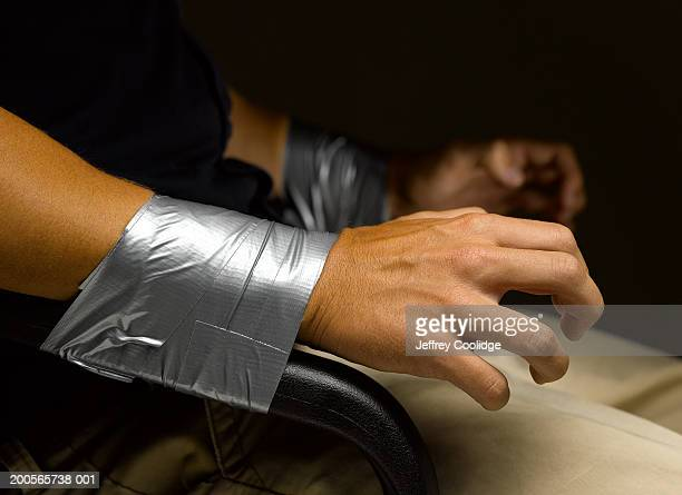 Man's wrists taped to arms of chair, close-up
