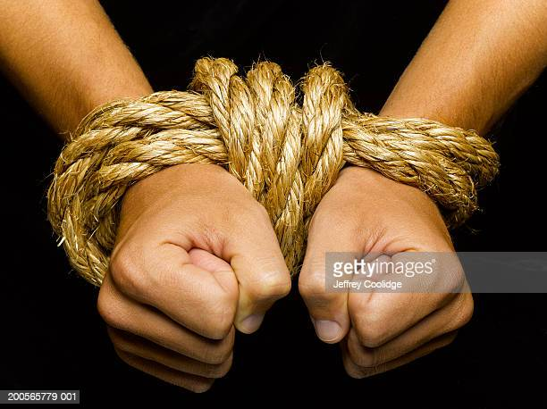 Man's wrists tied together with rope, close-up
