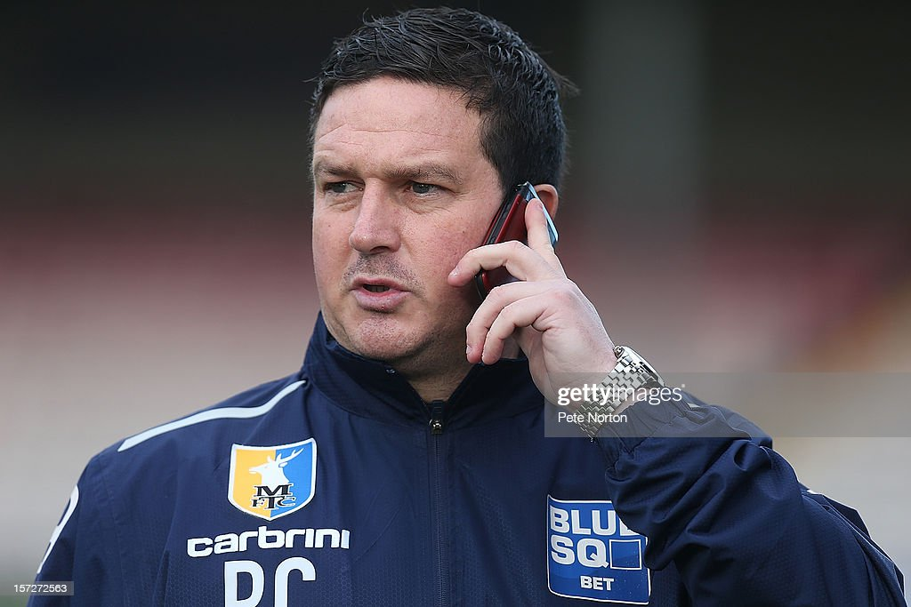 Mansfield Town manager Paul Cox talks on his mobile phone prior to the FA Cup with Budweiser Second Round match at Sincil Bank Stadium on December 1, 2012 in Lincoln, England.
