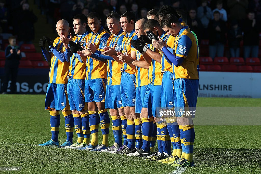 Mansfield Town players observe a minutes applause in memory of former Lincoln City player Bert Linnecor prior to the FA Cup with Budweiser Second Round match at Sincil Bank Stadium on December 1, 2012 in Lincoln, England.