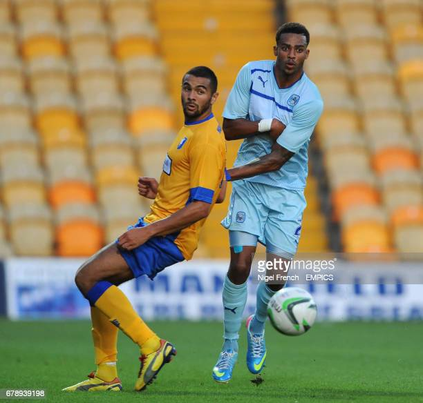 Mansfield Town's Calvin Andrews and Coventry City's Cyrus Christie battle for the ball