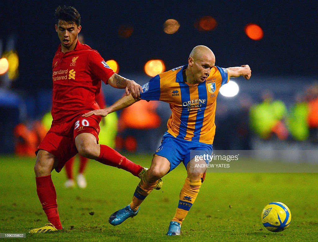 """Mansfield Town's English midfielder Lindon Meikle (R) vies with Liverpool's Spanish forward Suso during the FA Cup third round football match between Mansfield Town and Liverpool at Field Mill in Mansfield, central England, on January 6, 2013. USE. No use with unauthorized audio, video, data, fixture lists, club/league logos or """"live"""" services. Online in-match use limited to 45 images, no video emulation. No use in betting, games or single club/league/player publications."""