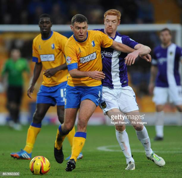Mansfield Town's John Dempster and Oxford United's Dave Kitson battle for the ball during the Sky Bet League two match at Field Mill Mansfield