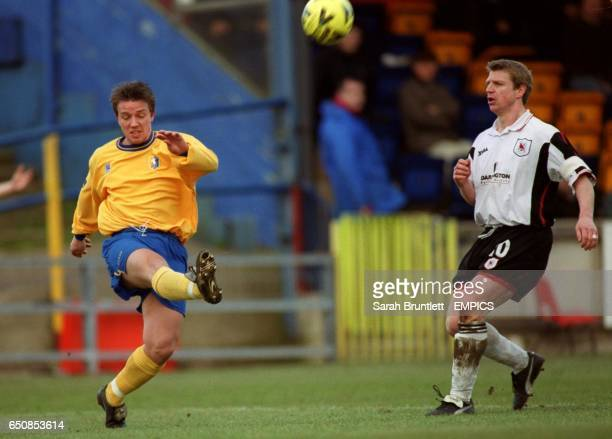Mansfield Town's Lee Cowling clears the ball under pressure from Darlington's Marco Gabbiadini
