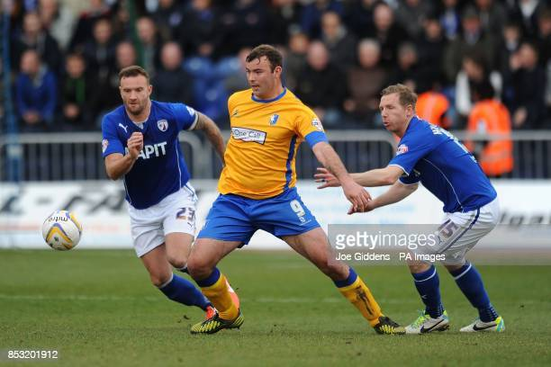 Mansfield Town's Matt Rhead and Chesterfield's Ian Evatt and Ritchie Humphreys battle for the ball during the Sky Bet League Two match at the One...