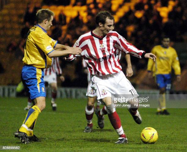 Mansfield Town's Tom Curtis challenges Lincoln City's Peter Gain for the ball during the Nationwide Division Three match at the Field Mill Ground...