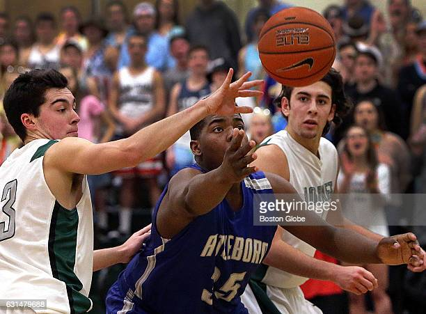 Mansfield's Sam Hyland at left and Attleboro's Qualeem Charles chase a loose ball Mansfield hosts Attleboro in a boys' high school basketball matchup...