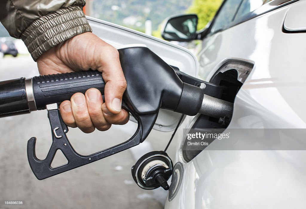 Mans's hand holding fuel nozzle in car