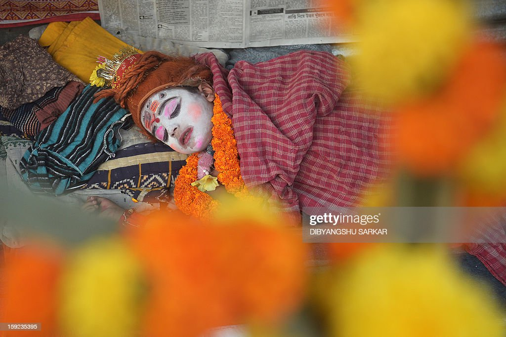 Mantu Das, 6, dressed as Hindu god Lord Shiva takes a nap at the Gangasagar temporary camp in Kolkata on January 10, 2013. Sadhus and Hindu pilgrims began to gather in Kolkata on their way to the annual Hindu holy festival Gangasagar Mela, where an expected hundred thousand Hindu pilgrims will gather at the Gangasagar to take a dip in the ocean at the confluence of the River Ganges and the Bay of Bengal, on the occasion of Makar Sankranti, a holy day of the Hindu calendar considered to be of great religious significance in Hindu mythology. AFP PHOTO/Dibyangshu SARKAR
