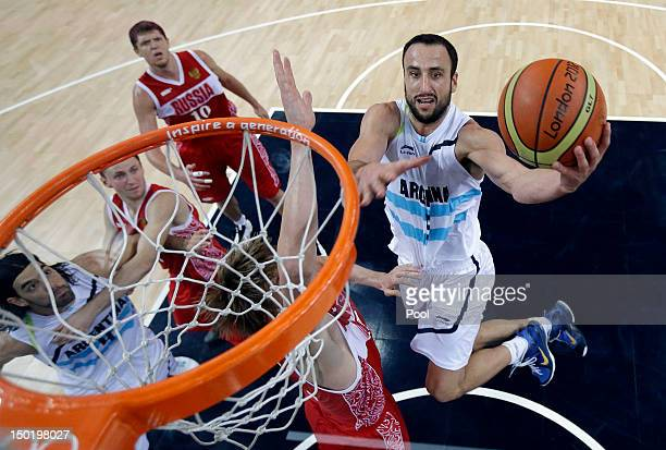 Manu Ginobili of Argentina drives to the basket against Andrei Kirilenko of Russia during the Men's Basketball bronze medal game between Russia and...