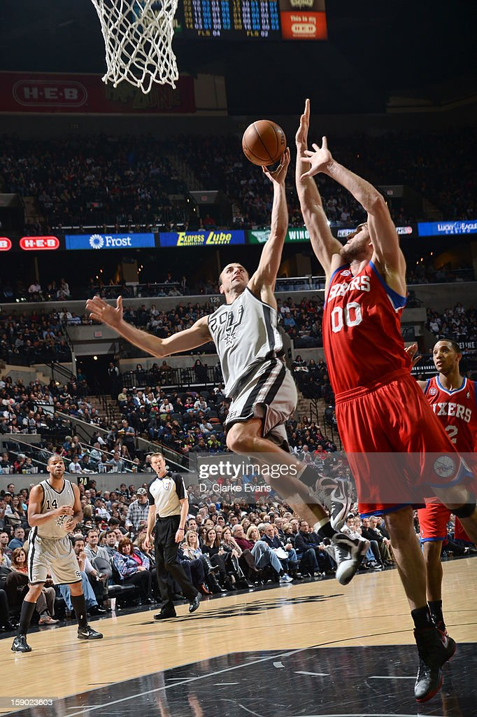 Manu Ginobili #20 of the San Antonio Spurs battle for the ball control with <a gi-track='captionPersonalityLinkClicked' href=/galleries/search?phrase=Spencer+Hawes&family=editorial&specificpeople=3848319 ng-click='$event.stopPropagation()'>Spencer Hawes</a> #00 of the Philadelphia 76ers during the game between the Philadelphia 76ers and the San Antonio Spurs on January 5, 2013 at the AT&T Center in San Antonio, Texas.