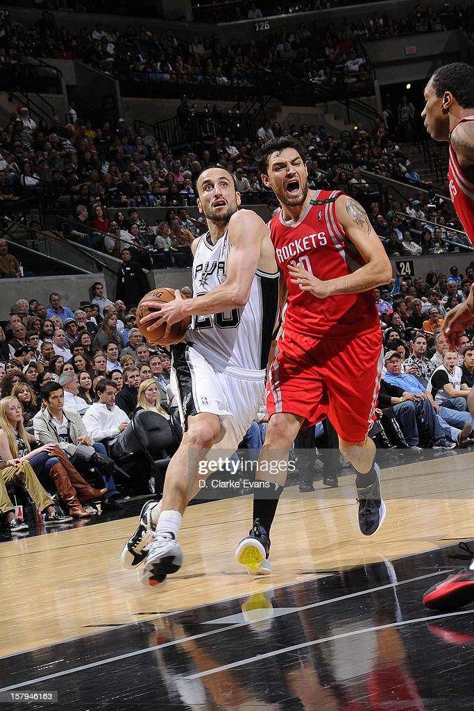 Manu Ginobili #20 of the San Antonio Spurs drives to the basket against <a gi-track='captionPersonalityLinkClicked' href=/galleries/search?phrase=Carlos+Delfino&family=editorial&specificpeople=206625 ng-click='$event.stopPropagation()'>Carlos Delfino</a> #10 of the Houston Rockets on December 7, 2012 at the AT&T Center in San Antonio, Texas.