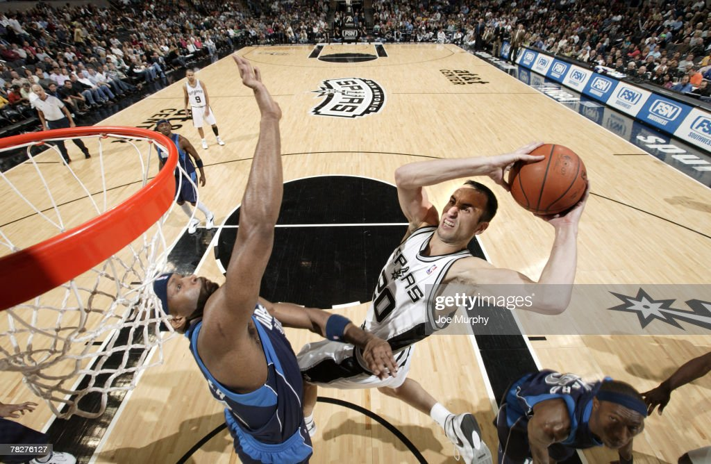 Manu Ginobili #20 of the San Antonio Spurs drives to the basket for a layup over Erick Dampier #25 of the Dallas Mavericks during a game on December 5, 2007 at the AT&T Center in San Antonio, Texas.