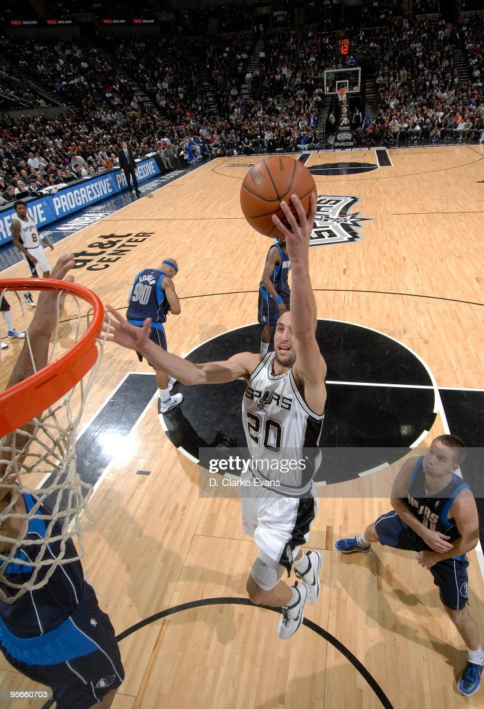 Manu Ginobili #20 of the San Antonio Spurs dunks past Jose Juan Barea #11 of the Dallas Mavericks on January 8, 2010 at the AT&T Center in San Antonio, Texas.