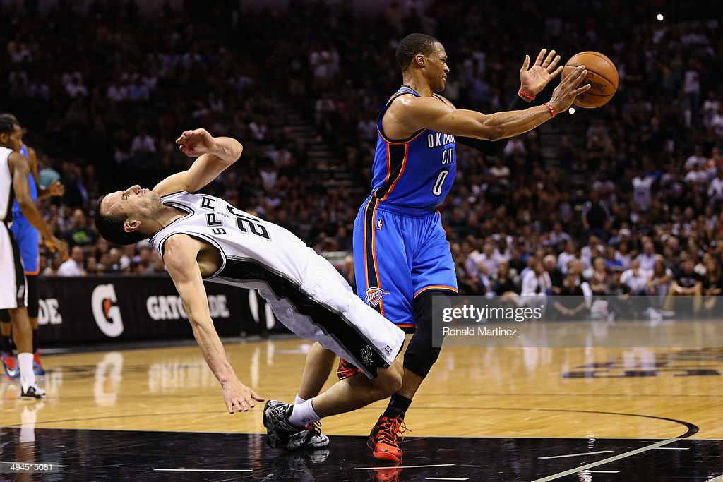 Manu Ginobili #20 of the San Antonio Spurs falls to the court after colliding with Russell Westbrook #0 of the Oklahoma City Thunder in the second half during Game Five of the Western Conference Finals of the 2014 NBA Playoffs at AT&T Center on May 29, 2014 in San Antonio, Texas.