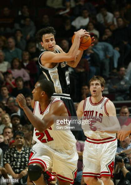Manu Ginobili of the San Antonio Spurs grabs a rebound as Andres Nocioni and Chris Duhon of the Chicago Bulls head down court at the United Center...