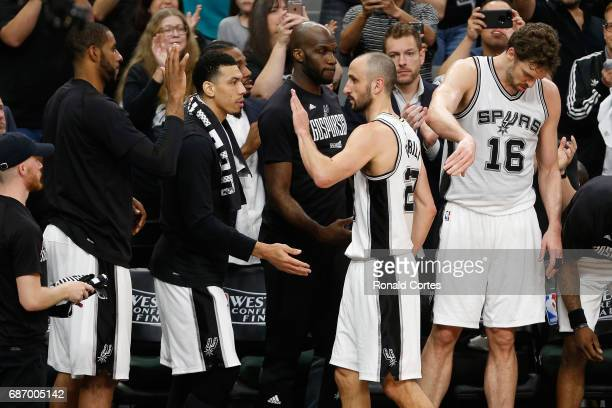Manu Ginobili of the San Antonio Spurs high fives teammates as he comes off the court in the second half against the Golden State Warriors during...