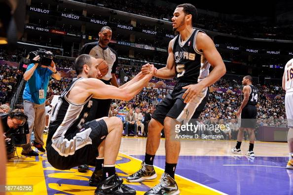Manu Ginobili of the San Antonio Spurs is helped up by teammate Cory Joseph while playing the Los Angeles Lakers in Game Four of the Western...