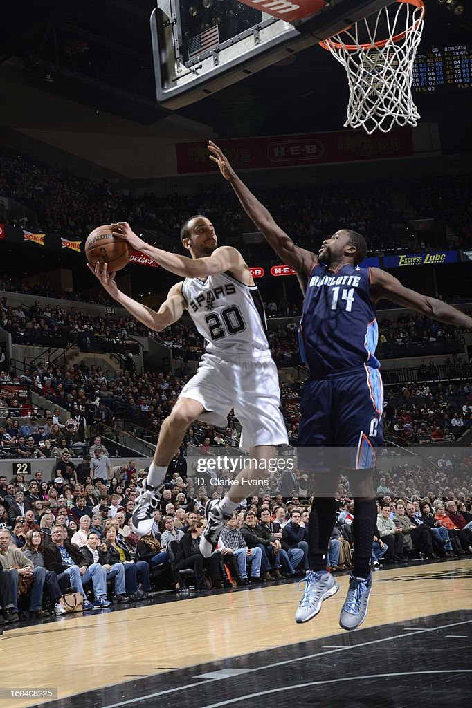 Manu Ginobili #20 of the San Antonio Spurs looks to pass in mid-air against Michael Kidd-Gilchrist #14 of the Charlotte Bobcats on January 30, 2013 at the AT&T Center in San Antonio, Texas.