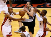 Manu Ginobili of the San Antonio Spurs loses the ball as he drives between Ray Allen and Dwyane Wade of the Miami Heat in overtime during Game Six of...