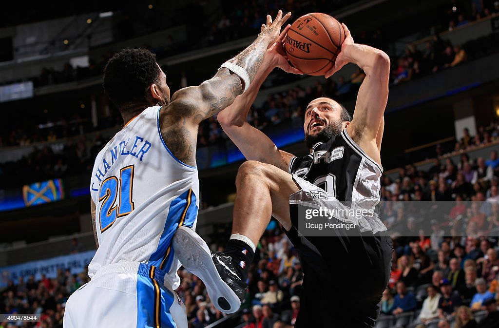 Manu Ginobili of the San Antonio Spurs makes a shot over Wilson Chandler of the Denver Nuggets at Pepsi Center on December 14 2014 in Denver Colorado...