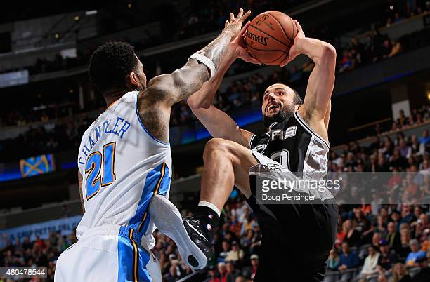 Manu Ginobili of the San Antonio Spurs makes a shot over Wilson Chandler of the Denver Nuggets at Pepsi Center on December 14 2014 in Denver Colorado...