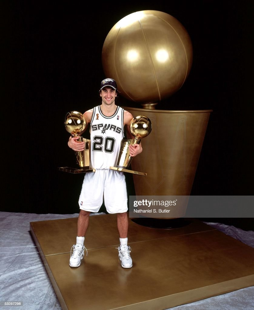 Manu Ginobili #20 of the San Antonio Spurs poses with two of his championship trophies after winning Game Seven of the 2005 NBA Finals June 23, 2005 at the SBC Center in San Antonio, Texas. The Spurs defeated the Pistons 81-74.
