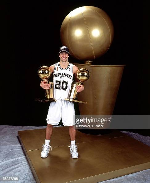 Manu Ginobili of the San Antonio Spurs poses with two of his championship trophies after winning Game Seven of the 2005 NBA Finals June 23 2005 at...
