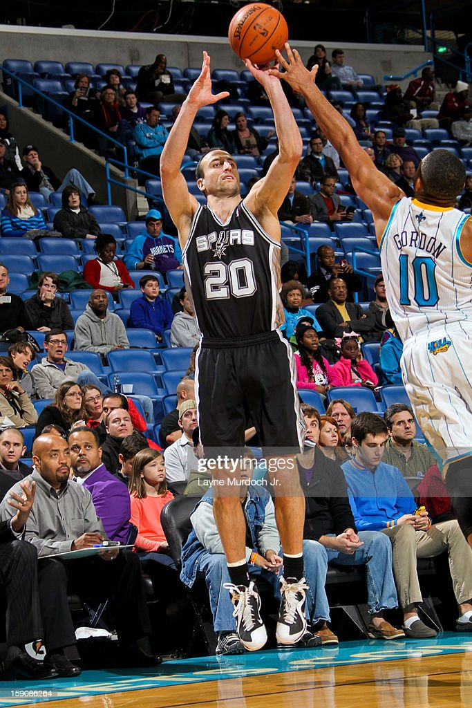 Manu Ginobili #20 of the San Antonio Spurs shoots a three-pointer against Eric Gordon #10 of the New Orleans Hornets on January 7, 2013 at the New Orleans Arena in New Orleans, Louisiana.