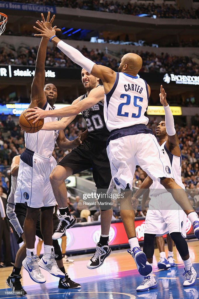 Manu Ginobili #20 of the San Antonio Spurs takes a shot against Vince Carter #25 of the Dallas Mavericks and Elton Brand #42 at American Airlines Center on December 30, 2012 in Dallas, Texas.