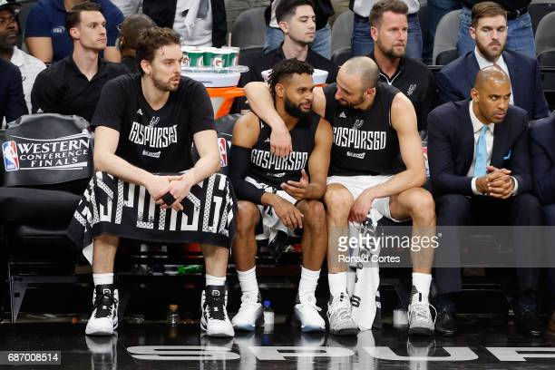 Manu Ginobili reacts on the bench with Patty Mills and Pau Gasol of the San Antonio Spurs in the second half against the Golden State Warriors during...