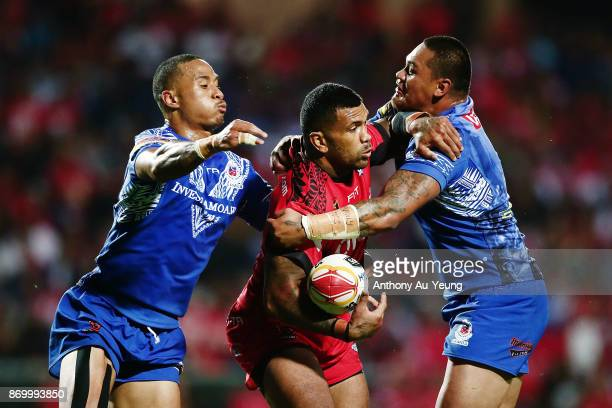 Manu Ma'u of Tonga is tackled by Joseph Leilua and Ben Roberts of Samoa during the 2017 Rugby League World Cup match between Samoa and Tonga at...