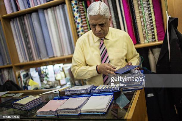 Manu Melwani coowner of Sam's Tailor arranges fabric samples at the company's store in the Tsim Sha Tsui district of Hong Kong China on Wednesday...