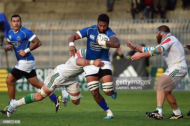 Manu Samoa lock Fa'atiga Lemalu is tackled by Italian defenders during the rugby union test match Italy vs Samoa in Ascoli Piceno on November 8 2014...