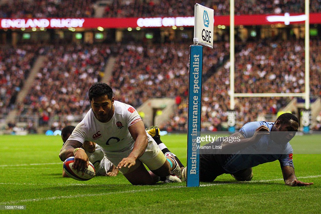 Manu Tuilagi of England crashes over the tryline to score his team's sixth try during the QBE international match between England and Fiji at...