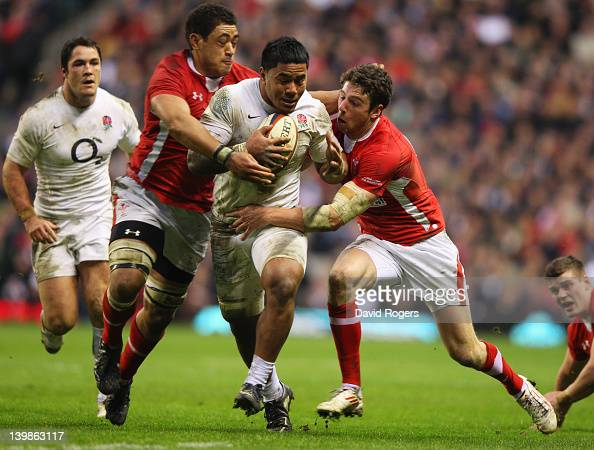 Manu Tuilagi of England is tackled by Toby Faletau and Alex Cuthbert of Wales during the RBS 6 Nations match between England and Wales at Twickenham...