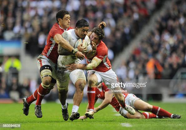 Manu Tuilagi of England is tackled by Toby Faletau and Alex Cuthbert of Wales during the RBS Six Nations match between England and Wales at...