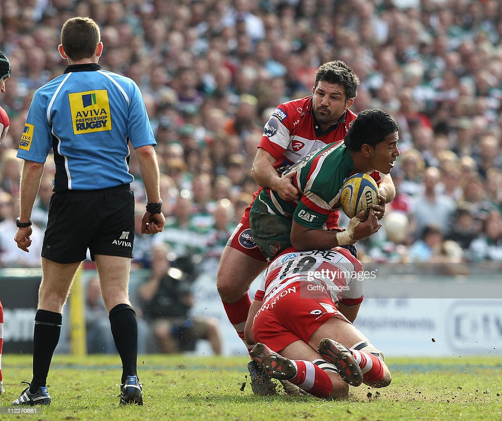 Manu Tuilagi of Leicester is tackled by Olivier Azam and Alex Brown during the Aviva Premiership match between Leicester Tigers v Gloucester at...