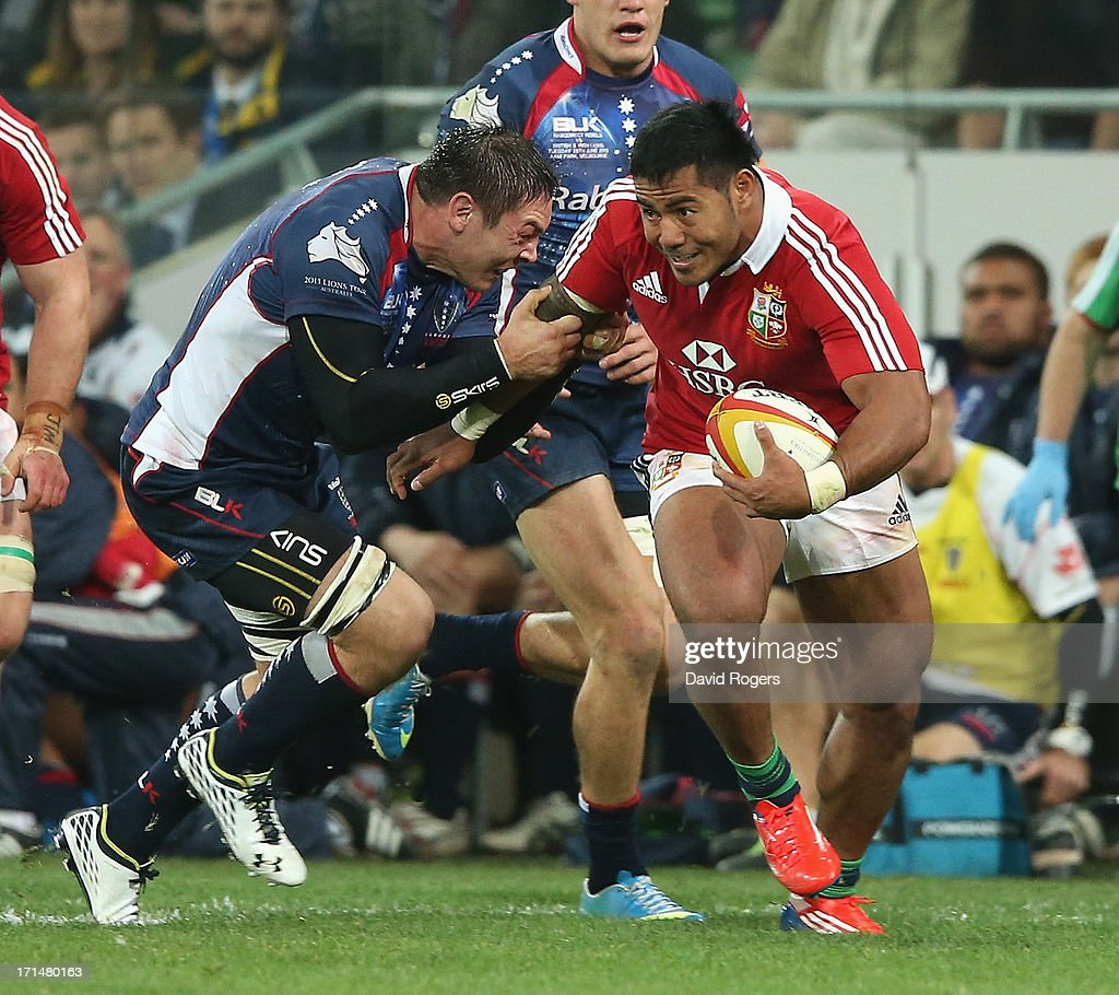 Manu Tuilagi of the Lions is tackled by Gareth Delve during the International Tour Match between the Melbourne Rebels and the British Irish Lions at...